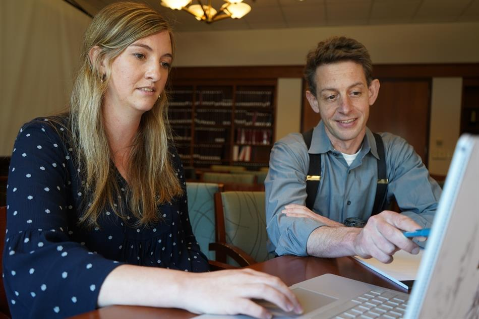 Elizabeth Fisher and Andy Hessick work at a computer.